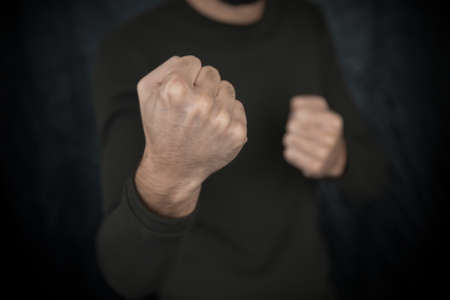 Caucasian man with a threatening gesture, ready to punch or fight with his fists. Zdjęcie Seryjne