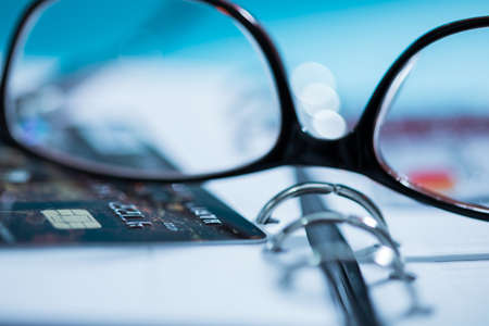 Glasses with credit card on notepad