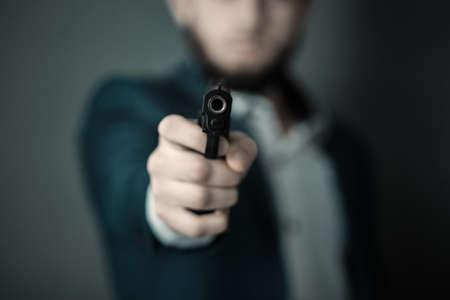 Man hand gun on dark background 스톡 콘텐츠