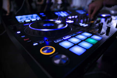 Professional dj with turntable player on stage in night club