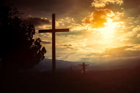 woman with cross at sunset Stock Photo