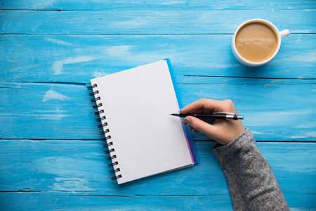woman hand notepad and coffee on desk