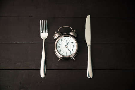 Alarm clock with fork and knife on the table