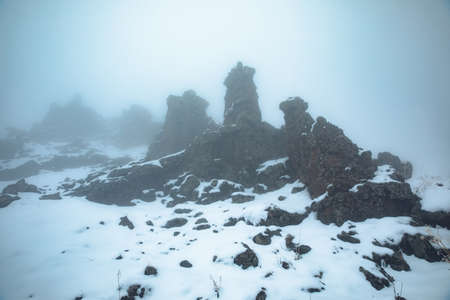 rocks in winter mountain with fog