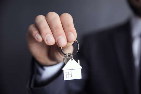 young business man hand holding house key