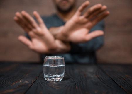 man hand stop sign glass of vodka on desk