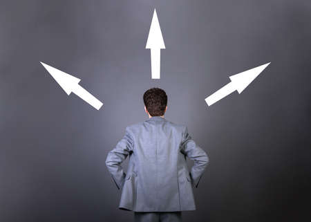 Young businessman taking a decision with different directed arrows above his head