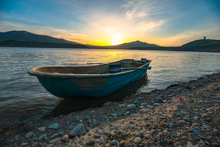 Old wooden boat on beach at sunset