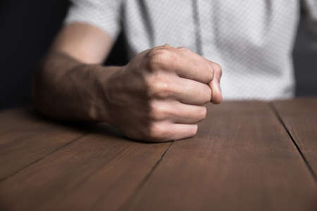 angry man fists on the table background Banco de Imagens
