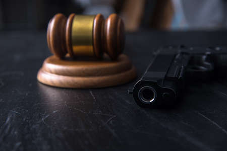 hammer gavel and gun on table