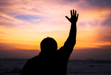 Human hands open palm up worship at the sunset