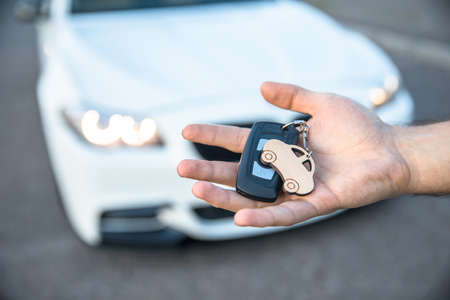 young man holding car key on car background