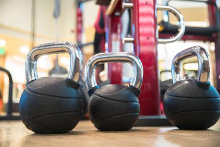 Sport equipment in gym. Dumbbells on floor. Standard-Bild