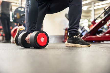 man building muscle and weight training with dumbbell at gym