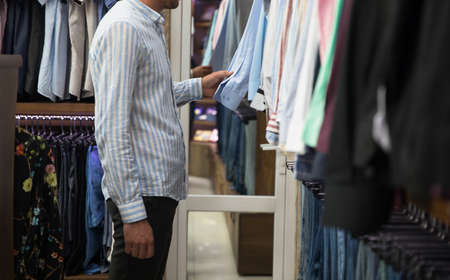 Young beautiful man shopping in fashion mall, choosing new clothes Standard-Bild