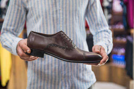 man holding brown shoes in shop