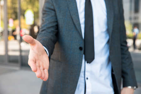 Young business man extend his hand in street