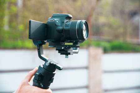 Man hand holding a gimbal stabilizer outdoor.