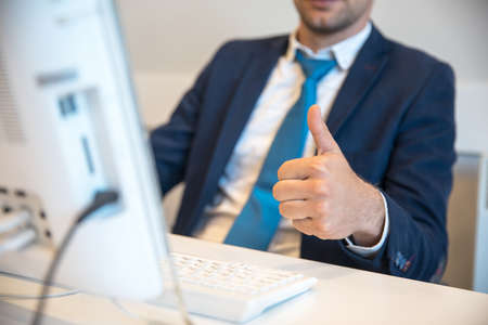 business man working in computer with okay sign