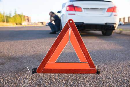 Traffic warning sign on road with car and driver