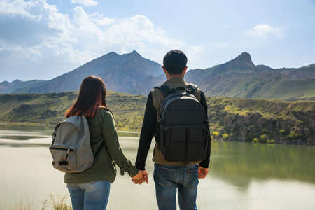 young couple hand in hand in lake background