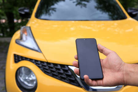 Man holding cell phone with car in background. Standard-Bild