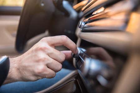 man hand in Button on dashboard in car panel Standard-Bild