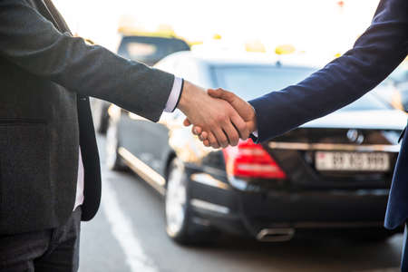 business man shaking hands with client in car dealership