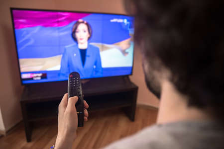 young man watching tv and use remote controller