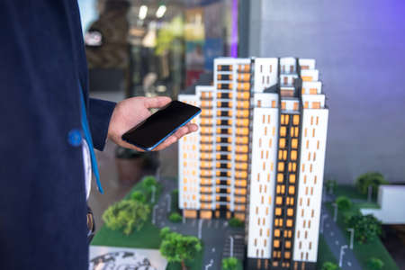 man holding phone with house models on table Standard-Bild