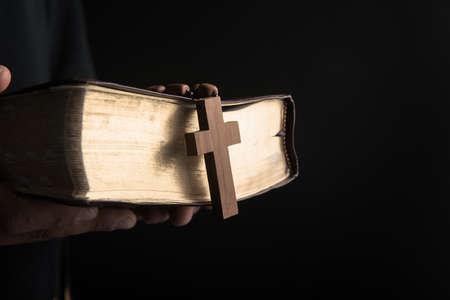 prayer man holding Holy Bilbe with cross Standard-Bild