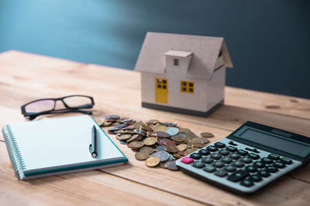 finance concept, house model with claculator and coins Standard-Bild
