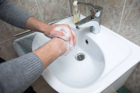 Man washing hands with water and soap in bathroom