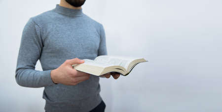 Young man holding Holy Bible.