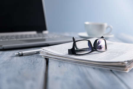 glasses on newspaper and computer on table