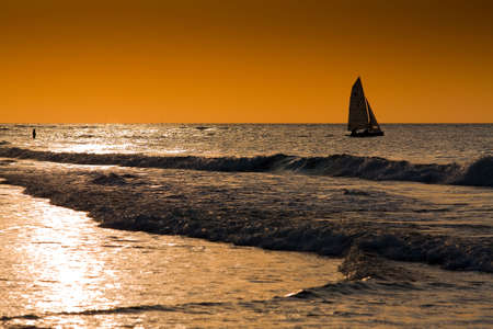 sailingboat: Sailing boat in front of sunset leaves a person at the coast Stock Photo