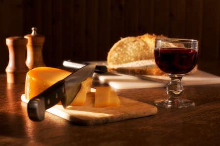 slinky: Dinner in a sunset mood ( rustic wine, bread cheese, pepper, salt ) Stock Photo