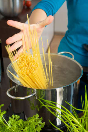 to let: Woman let falls spaghetti into water Stock Photo