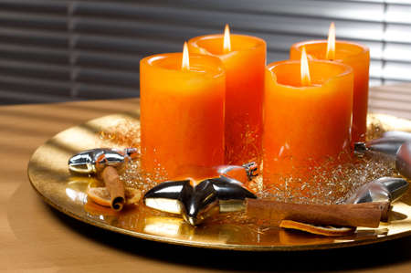snugly: Four candles decorated on a golden plate Stock Photo