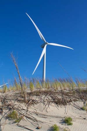 Wind power energy turbine behind a dune photo