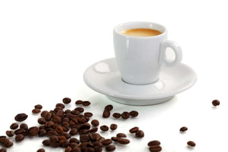 coffe beans: White espresso cup surrounded by coffe beans