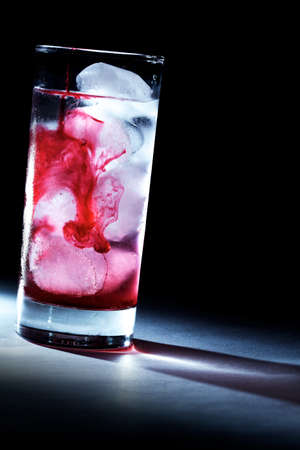 Pouring red syrup  juice in glass of water with ice cubes, backlit photo