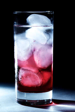 Red syrup  juice in glass of water with ice cubes, backlit photo