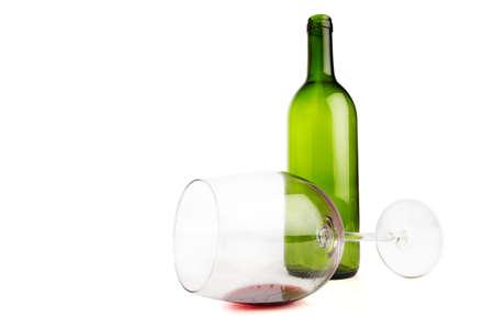 Empty wine glass lying in front of an empty green wine bottle photo