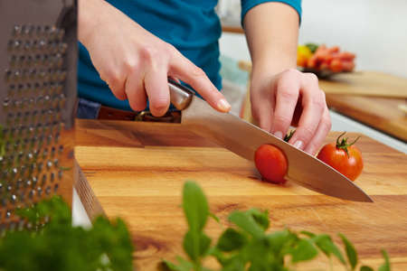 cutting boards: Woman slicing tomatoes on carving board with knife
