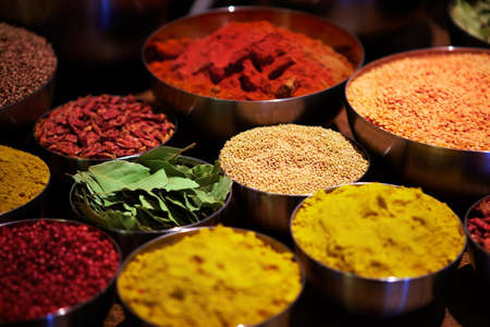 Some metal bowl filled with an assortment of different coloured spices photo