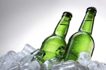Two beer bottles on on cubes over white background photo