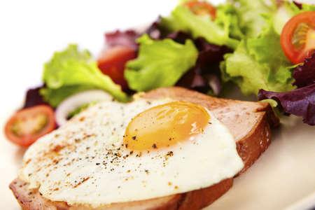 Liver loaf, meatloaf and fried egg on mixed salad photo