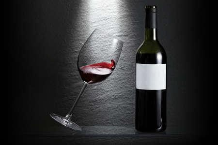 tilt: Wave in a tilting wine glass beside a bottle