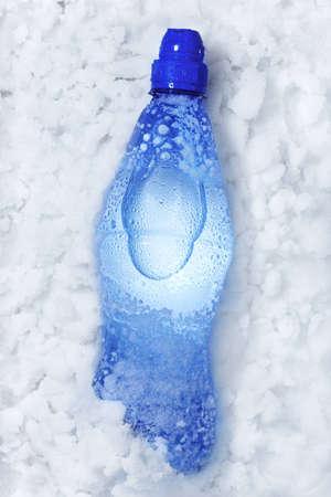 ice crushed: Blauwe soda fles liggend op witte sneeuw